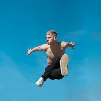 Het vooraanzicht van shirtless hiphopuitvoerder stelt mid-air