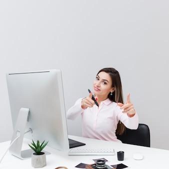 Het vooraanzicht van vrouw bij bureau het geven beduimelt omhoog