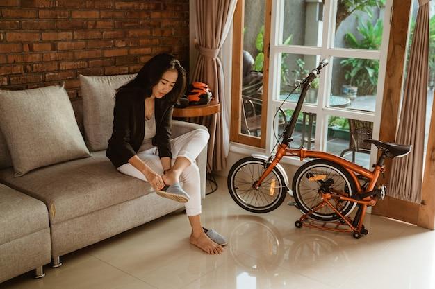 Het voorbereiden van de aziatische zitting van de vrouwenarbeider op bank die schoenen draagt