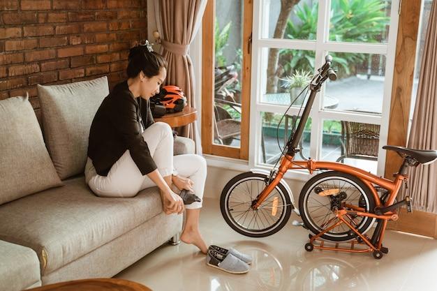 Het voorbereiden van de aziatische zitting van de vrouwenarbeider op bank die sokken dragen