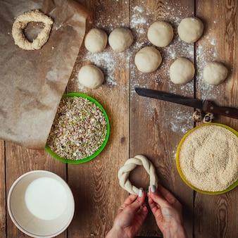 Het voorbereiden van deeg cirkel door vrouwelijke handen om simit brood bovenaanzicht te bakken