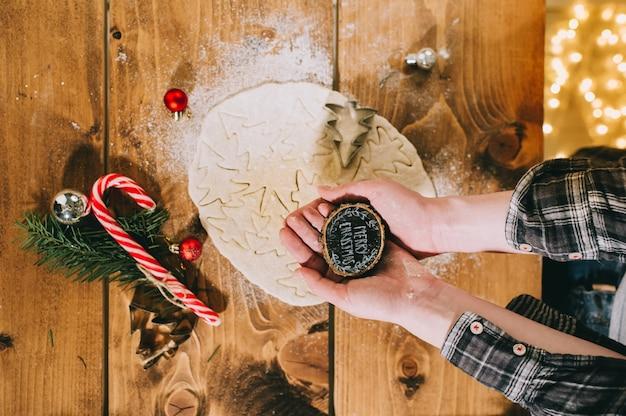 Het voorbereiden van kerstkoekjes op een houten oppervlak