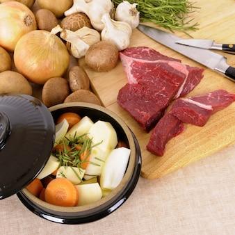 Het voorbereiden van rundvlees voor braadpan of hutspot met ingrediënten en mes op keuken hakbord.