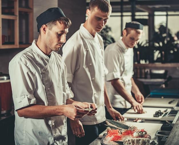 Het voorbereiden van sushi die in restaurantkeuken wordt geplaatst
