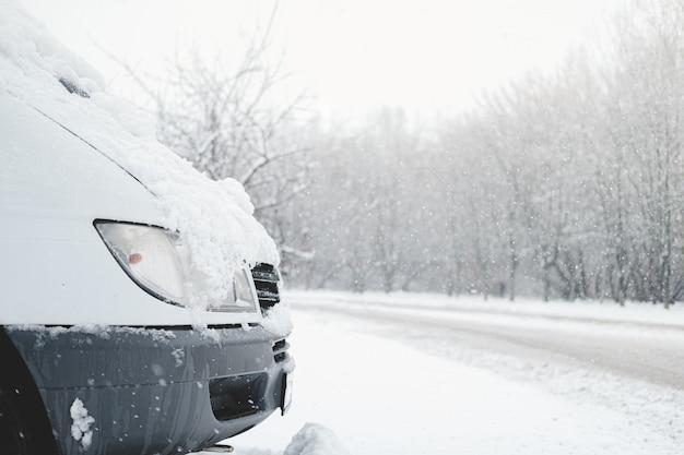 Het voorste deel van een auto bedekt met sneeuw. voertuig staat aan de besneeuwde weg bij stormachtig weer
