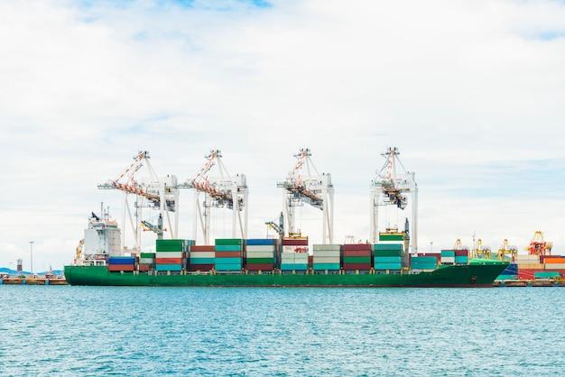 Het vrachtschip van de containerlading met werkende kraanbrug in scheepswerf bij schemer voor logistische invoer-uitvoer
