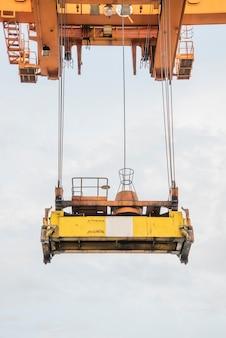 Het vrachtschip van de containerlading met werkende kraanlaadbrug in scheepswerf bij logistische invoer-uitvoer