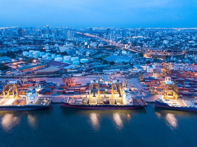Het vrachtschip van de containerlading met werkende kraanlaadbrug in scheepswerf bij schemer voor logistische invoer-uitvoer