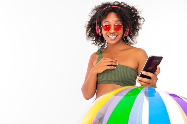 Het vrij afrikaanse wijfje in zwempak bevindt zich met grote kleurrijke rubberbal, luistert aan muziek met oortelefoons en doet selfie geïsoleerd