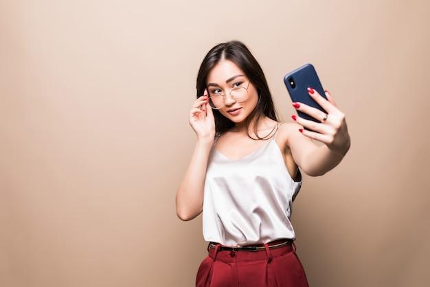 Het vrij aziatische meisje neemt selfie met haar slimme telefoon die op beige muur wordt geïsoleerd.