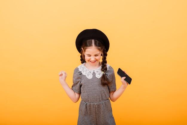 Het vrij glimlachende meisje houdt smartphone. leuk kind op gele achtergrond, modern kinderenconcept.