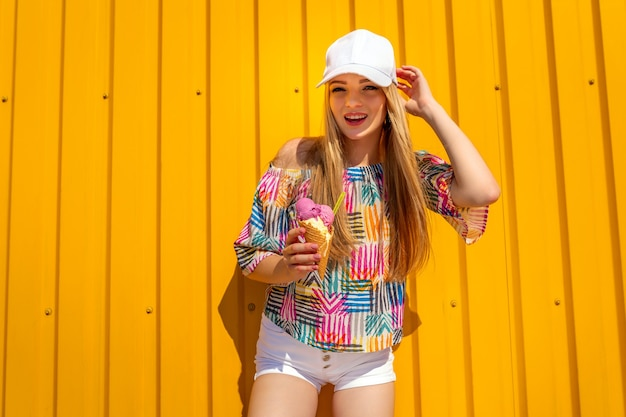 Het vrij jonge meisje van de hipsterstijl heeft pret openlucht in witte glb en het eten van roomijs op geel