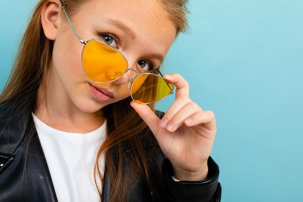 Het vrij kaukasische tienermeisje met lang bruin haar in zwart jasje en denimjeans houdt gele zonnebril die op blauwe achtergrond wordt geïsoleerd