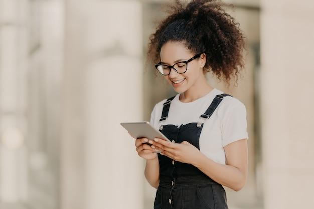 Het vrij krullende haired meisje bekijkt het digitale tabletscherm met glimlach, leest wat tekst of elektronisch boek