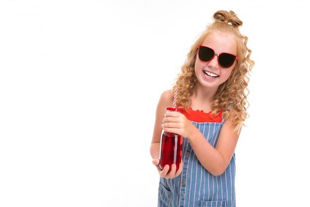 Het vrij modieuze kind met krullend haar drinkt een sap en glimlacht dat op wit wordt geïsoleerd