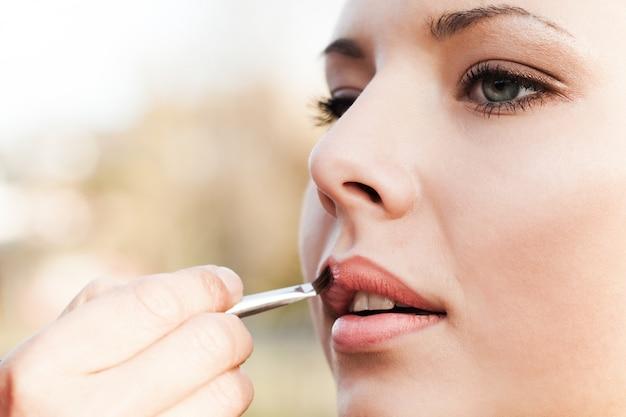 Het vrij mooie jonge meisje kleurt haar lippen