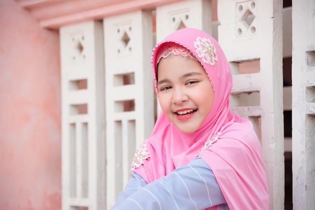 Het vrij moslimmeisje bekijkt camera en glimlacht.