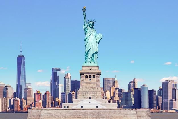 Het vrijheidsbeeld met het one world trade-bouwcentrum over de rivier de hudson en de stadsgezichtachtergrond van new york, oriëntatiepunten van de stad new york van lower manhattan.