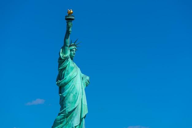 Het vrijheidsbeeld onder de blauwe hemelachtergrond