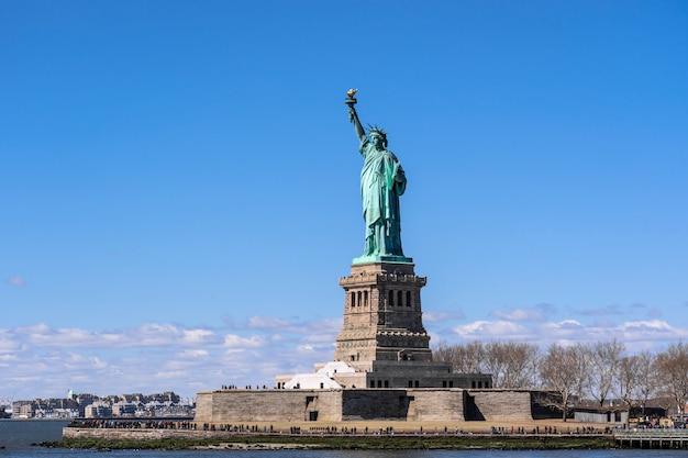 Het vrijheidsbeeld onder de blauwe hemelmuur, de stad van lower manhattan, new york