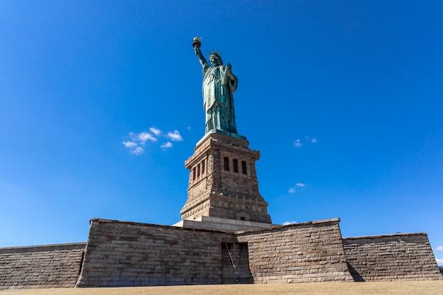 Het vrijheidsbeeld onder de blauwe luchtmuur, lower manhattan, new york city, architectuur en gebouw