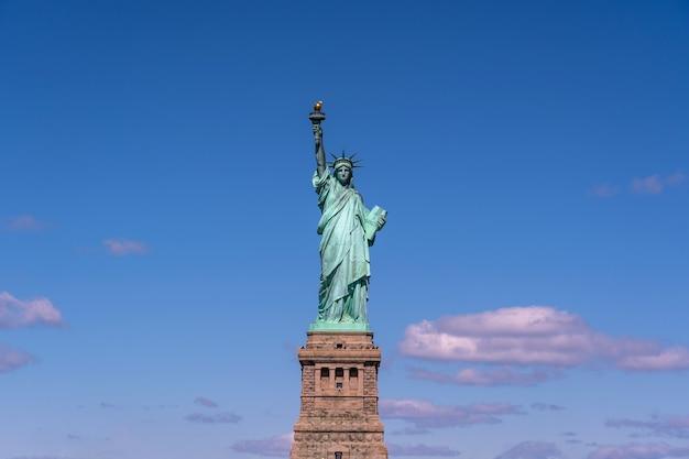 Het vrijheidsbeeld onder de blauwe luchtmuur, new york city