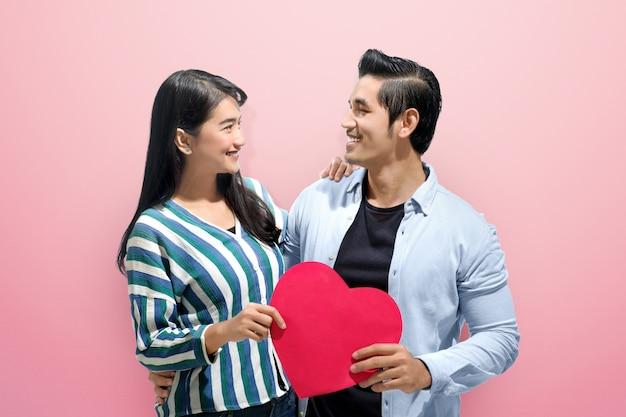 Het vrolijke aziatische paar omhelst en houdt rode document harten