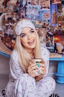 Het vrolijke blondemeisje drinkt koffie in pyjama's. slaapmasker. conceptenlevensstijl, rust, ontbijt, slaap.
