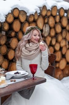 Het vrolijke blondemeisje met krullend haar houdt een cupcake. selectieve aandacht op de cupcake.