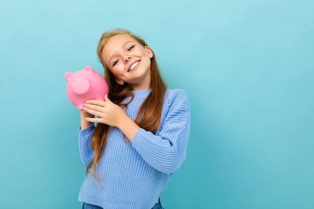 Het vrolijke charismatische schoolmeisje stellen met een spaarvarken voor geld