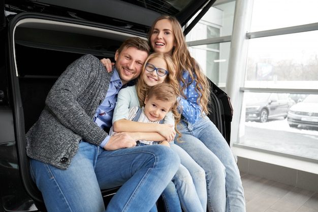 Het vrolijke familie stellen in autoboomstam van auto.