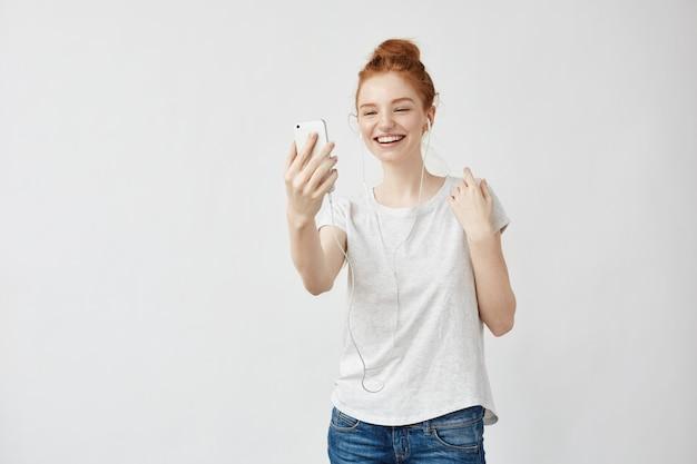 Het vrolijke foxy vrouw glimlachen die op telefoon in hoofdtelefoons spreekt.