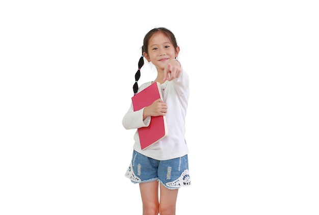 Het vrolijke glimlachende aziatische boek van de meisjegreep dat op witte achtergrond wordt geïsoleerd. kind omhelst een notitieboekje en wijst naar de camera.