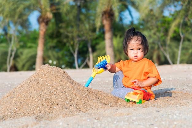 Het vrolijke grappige gravende speelstuk speelgoed van het dochtermeisje met zand