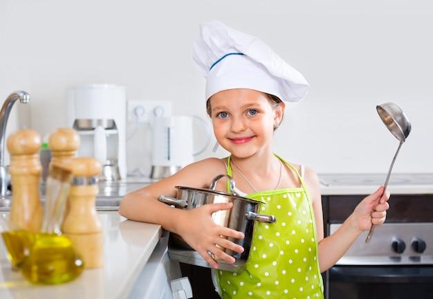 Het vrolijke het glimlachen meisje stellen met pan
