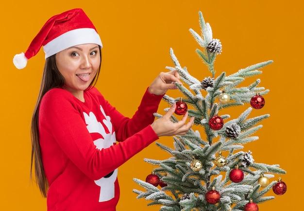Het vrolijke jonge aziatische meisje dat kerstmishoed met sweater draagt, verfraait de kerstboom die tong toont die op oranje muur wordt geïsoleerd