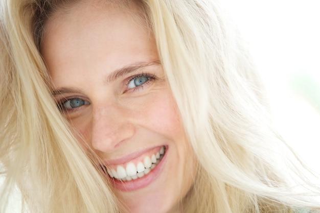 Het vrolijke jonge blonde vrouw glimlachen