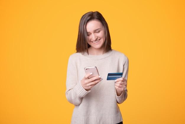 Het vrolijke jonge meisje geniet van mobiel en webbankieren op gele achtergrond.
