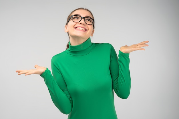 Het vrolijke jonge meisje in glazen die in studio stellen haalt in verrassing op en ziet omhoog eruit