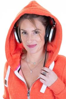 Het vrolijke jonge meisje van de blondevrouw in het sportieve sweater stellen geïsoleerd op wit luistert muziek met hoofdtelefoons