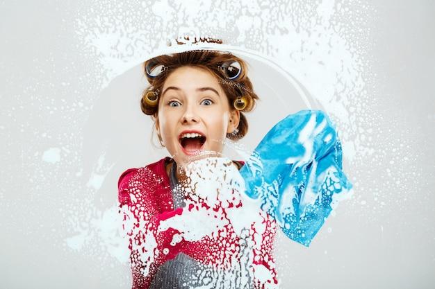Het vrolijke jonge meisje wast vensters met blauwe handdoek