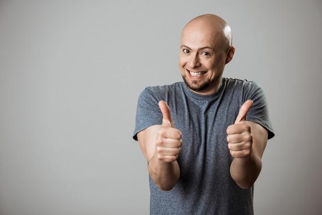 Het vrolijke jonge mens glimlachen, die ok over beige muur tonen