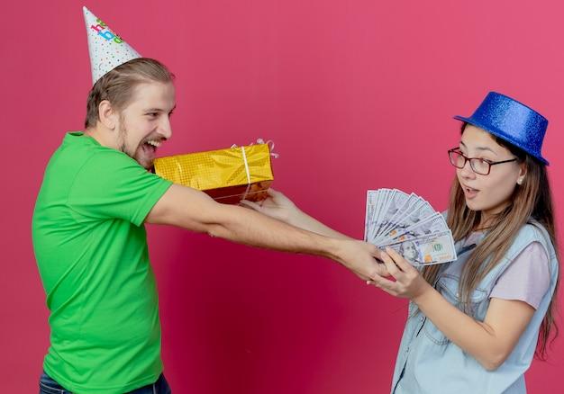 Het vrolijke jonge paar dat partijmutsen draagt bekijkt elkaar die giftdoos en geld houden die op roze muur wordt geïsoleerd