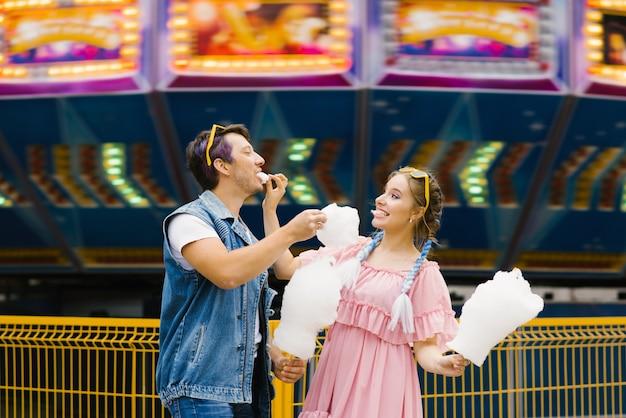 Het vrolijke jonge paar in liefde die in een pretpark rusten en elkaar suikerspin voeden. liefdesdag, valentijnsdag