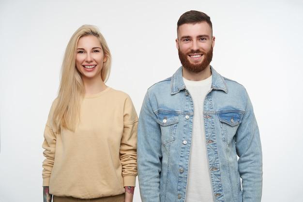 Het vrolijke jonge paar kleedde zich in vrijetijdskleding die hun handen met brede glimlach naar beneden houden, die op wit wordt geïsoleerd