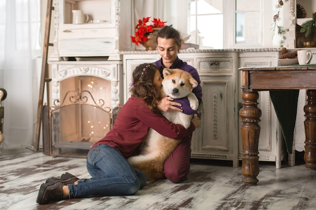 Het vrolijke jonge paar koestert en kust een hond van ras akita inu