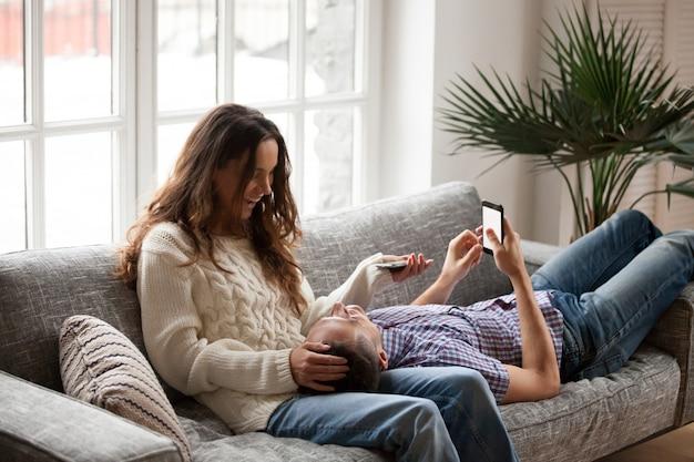 Het vrolijke jonge paar ontspannen op bank die en smartphones spreekt houdt