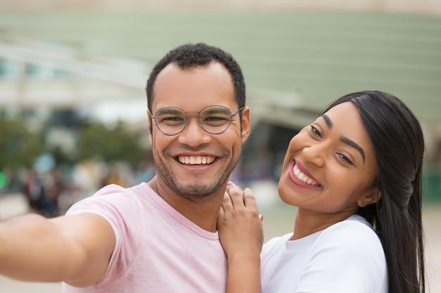 Het vrolijke jonge paar stellen voor selfie op straat