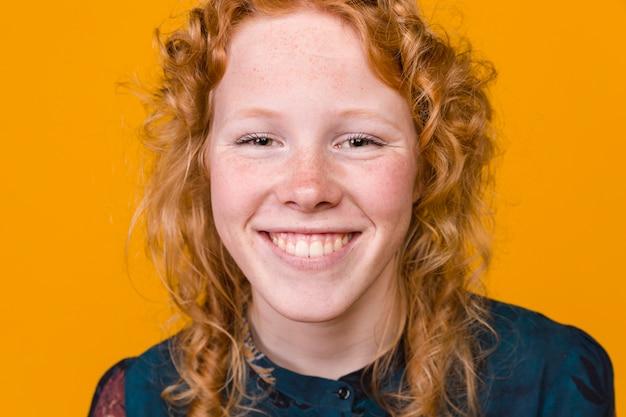 Het vrolijke jonge redhead vrouw glimlachen