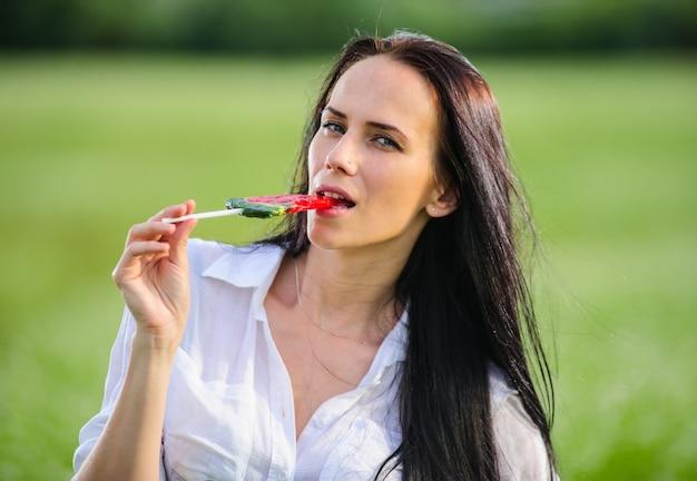 Het vrolijke jonge suikergoed van de vrouwenholding in de vorm van watermeloen snijdt dichtbij haar gezicht, het kijken. meisje rust in de natuur met lollies.